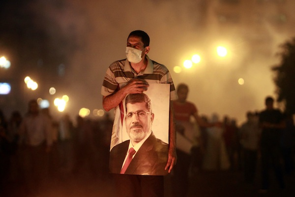 An injured supporter of deposed Egyptian President Mohamed Mursi carries a poster of Mursi as they run from tear gas fired by riot police during clashes on the Sixth of October Bridge over the Ramsis square area in central Cairo
