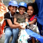 3 little girls giggle for the camera, waving a blue flag (my fav pic)